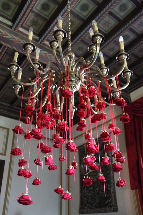 [Image description: A chandelier with dozens of red roses hanging from it decorates a ceiling. Image source: Pinterest]