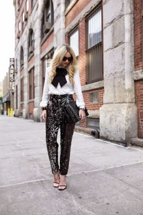 black sequin pants, a white long sleeve blouse with a black bow and heels