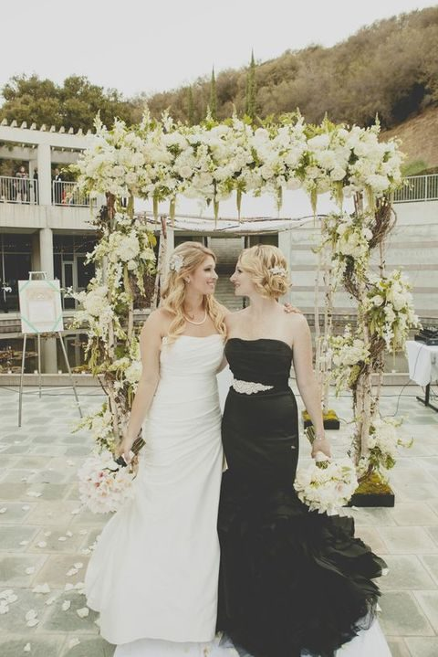 a bride in a black mermaid dress and a bride in a simple ivory one