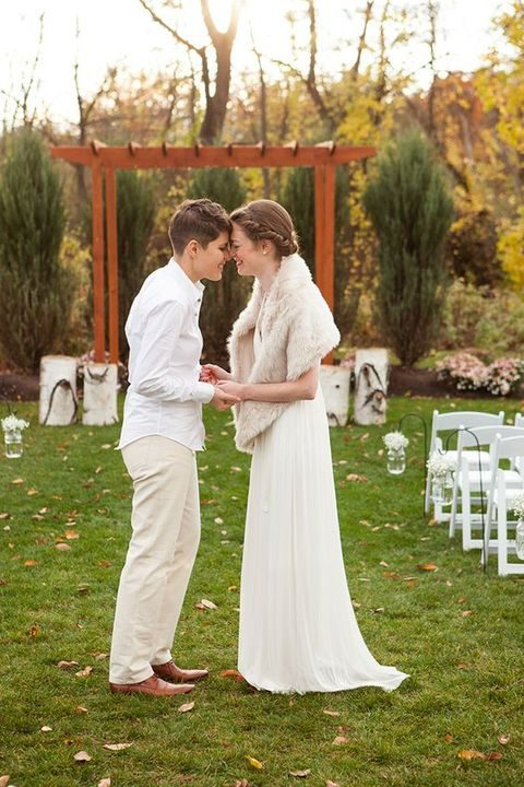 a bride in pants and a shirt and a bride in an ivory dress and a fir wrap