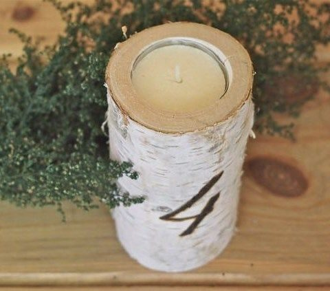 birch log candle holders with tablenumbers written