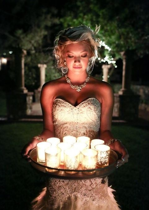 bride carrying candle holders on a tray