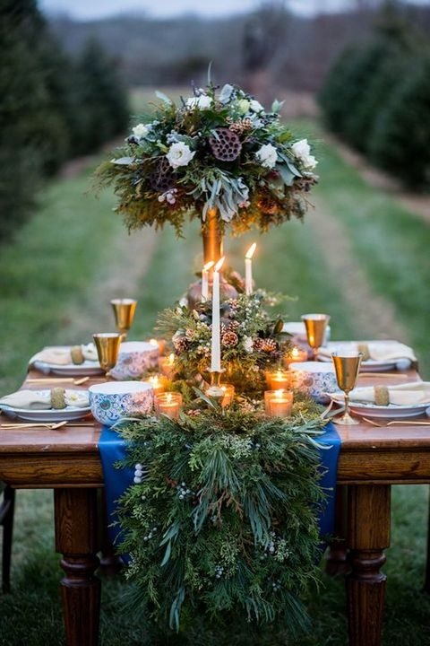 candles in an evergreen table runner with pinecones