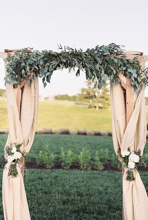 classic fabric-draped arch topped with lush eucalyptus leaves