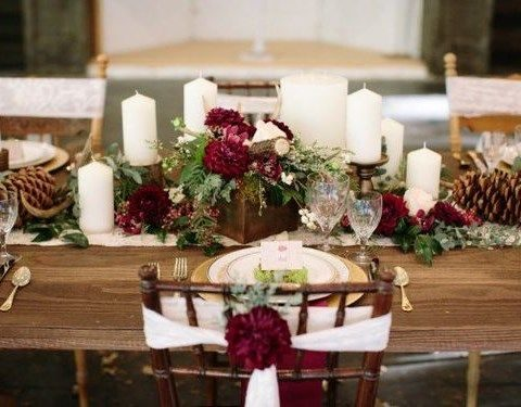 dark red flowers, pinecones and candles