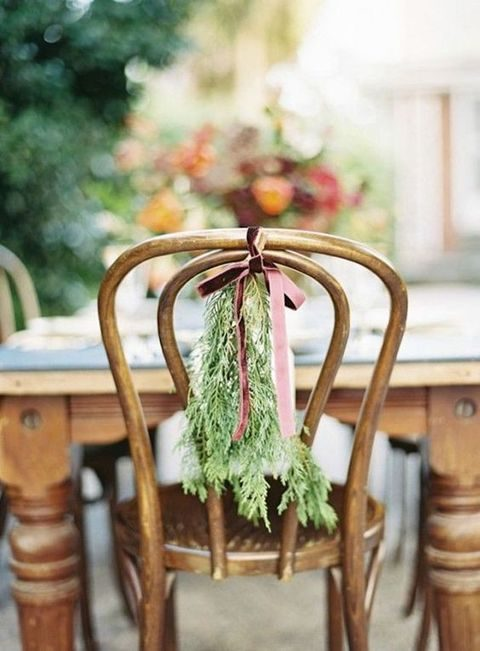 evergreen branches tied to chairs