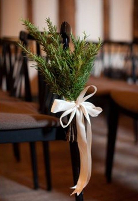 evergreen branches tied to the aisle chairs