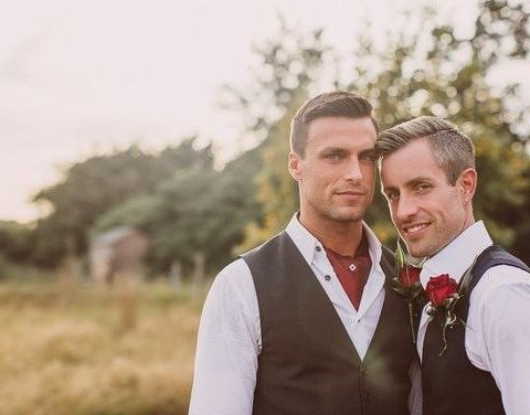 grooms in white shirts and vests, red rose boutonnieres