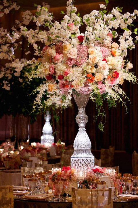 guest tables were topped with lush arrangements of flowers housed in crystal vases