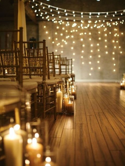 hang lights as a ceremony backdrop and echo it placing candles along the aisle