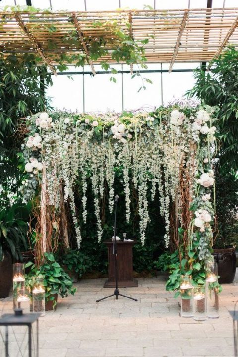 lush floral wedding arch with hanging elements