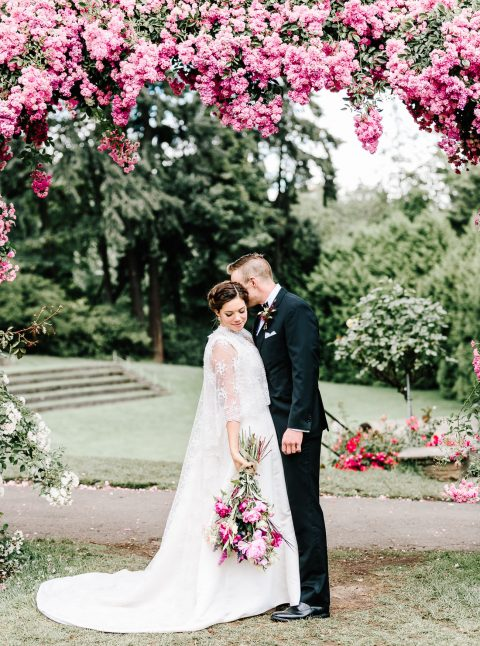 lush pink floral wedding arch in a grden