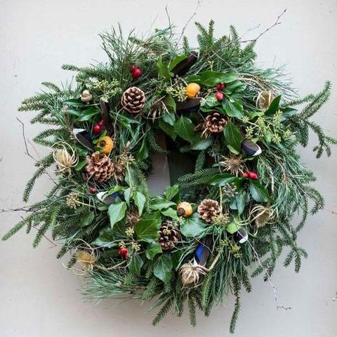 messy wreath with pinecones, whistles and berries