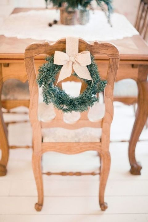 mini evergreen wreaths with neutral bows on chairs