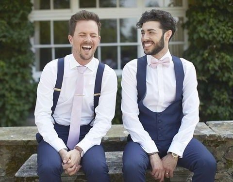 navy pants, a navy vest and a blush bow tie for one groom, navy suspenders and a blush tie for the second