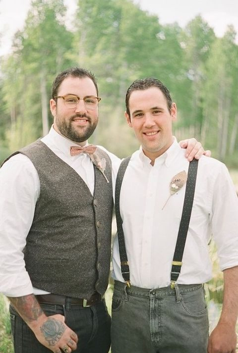 one groom in suspenders, the other rocking a vest for a vintage wedding