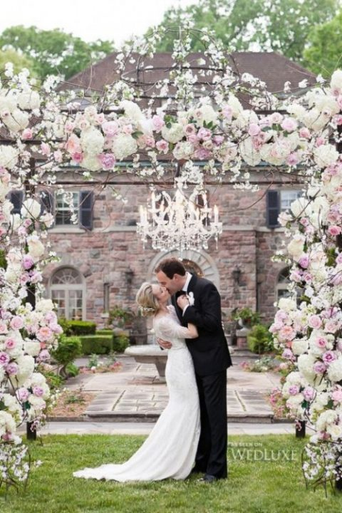 pink and ivory arch with a chandelier