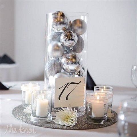 silver ornaments in a tall jar and a table number attached