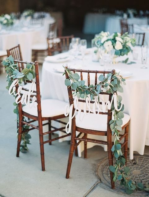 sweetheart chairs decorated with eucalyptus garlands