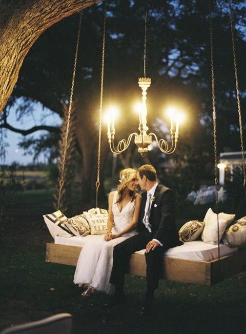 the couple sitting on a swing bed in the garden, lit with a chandelier