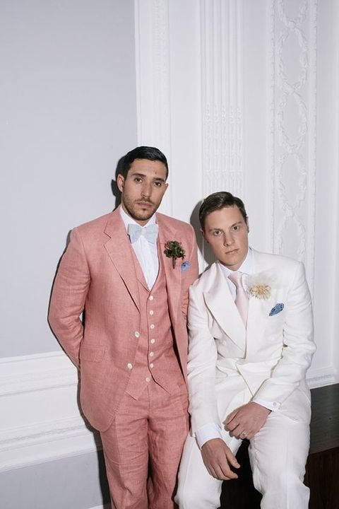 the first groom in a pink suit with a grey bow tie, the second groom in a cream suit with a blush tie