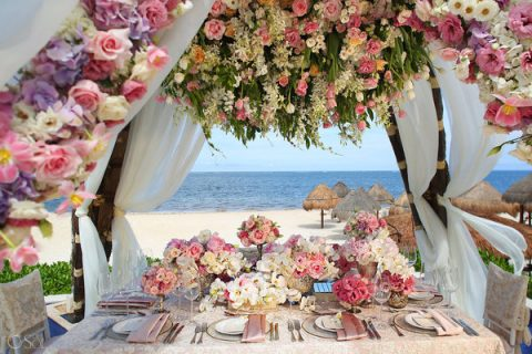 tropical reception with lush hanging florals over it