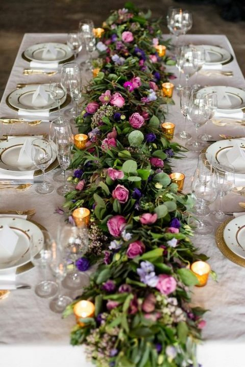 wedding reception tabletop with lush floral garland and candles