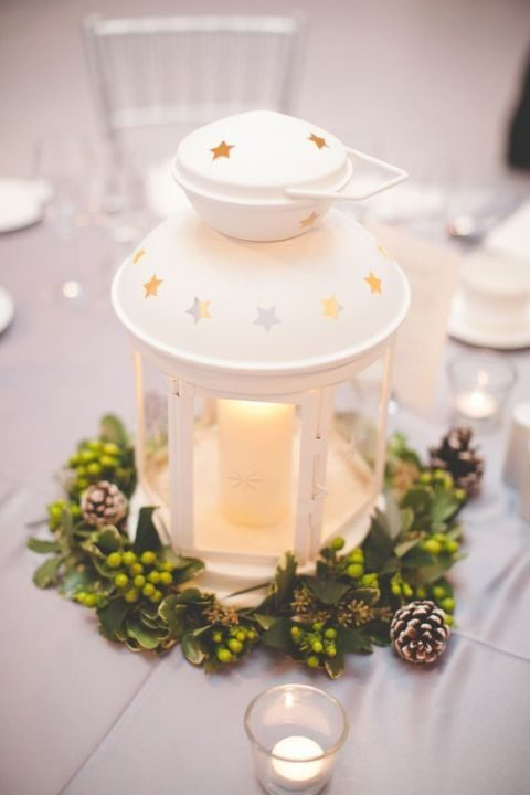 white candle lantern decorated with a green and pinecone wreath