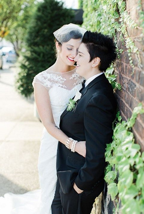 white illusion neckline wedding dress with lace appliques and a black tux