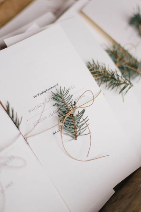 winter wedding program with evergreen branches attached