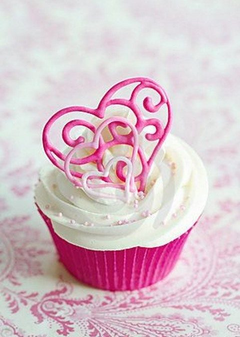 a Valenttine cupcake in a pink cover and with pink heart toppers