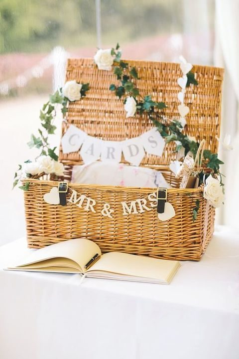 a basket for guest cards decorated with flowers