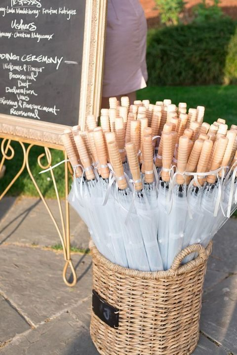 a basket of clear umbrellas for wedding guests