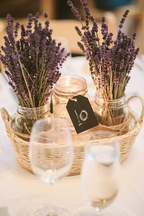 a basket with a candle lantern and lavender in jars