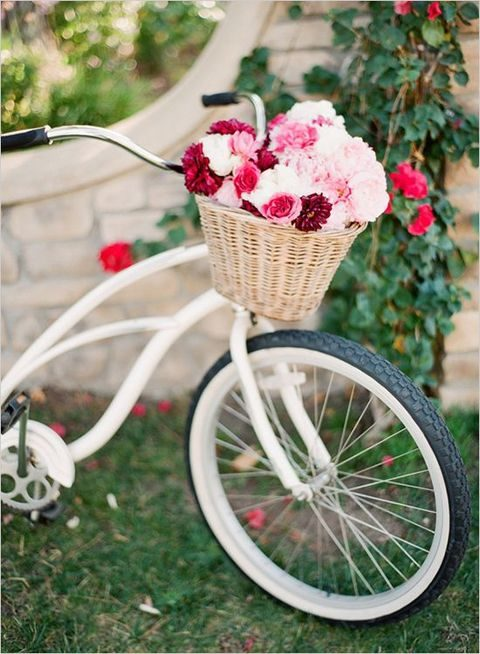a bike decorated with a basket full of flowers