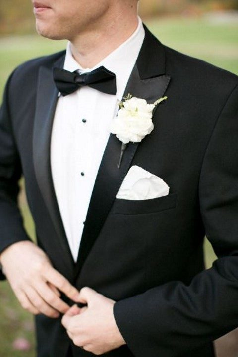 a black tuxedo and a white flower boutonniere