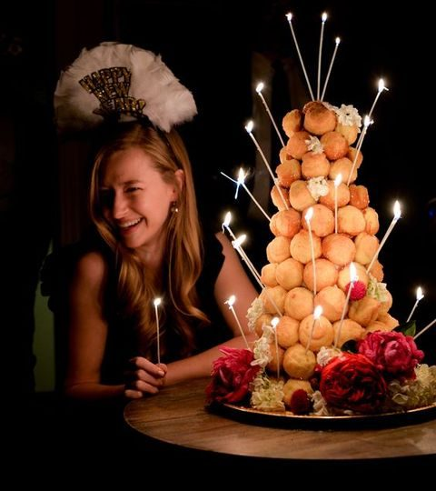 a croquembouche with candles and flowers