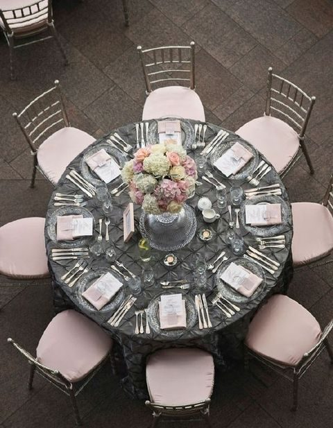 a dark grey tablecloth contrasts with blush chairs, flowers and menus