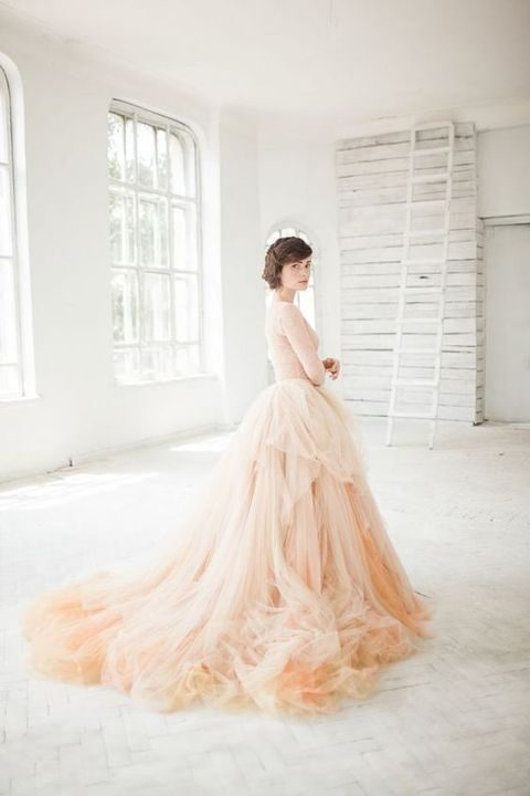 a frothy skirt consists of layers upon layers of soft tulle in layered shades of nude, sand, and peach for a dreamy ombré effect