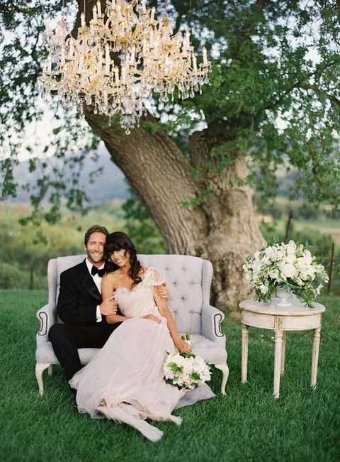 a glam chandelier, a vintage sofa and an antique table with flowers