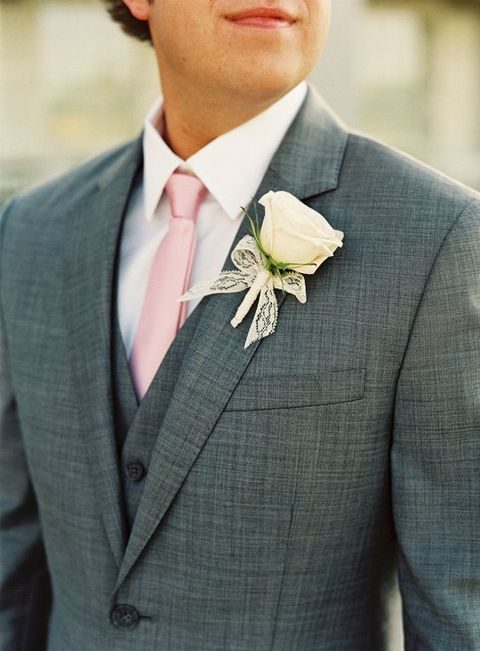 a grey suit with a pink tie and an ivory rose boutonniere
