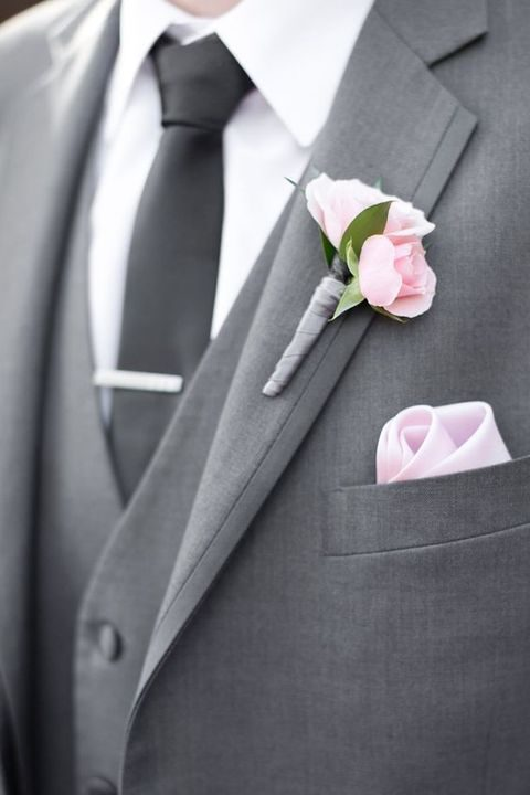 a grey suit with a pink tie and bloom boutonniere