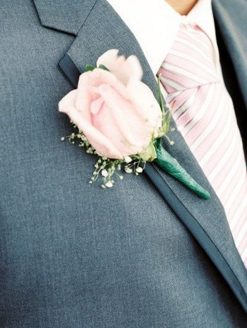 a grey suit with a striped pink tie and a pink rose