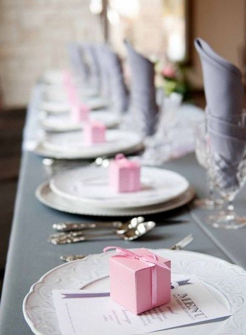 a grey tablecloth and napkins, pink favor boxes