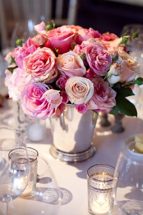 a lush centerpiece with various kinds of pink roses