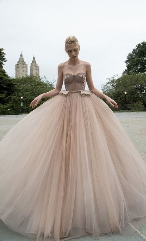 a nude princess gown, with fitted corset, floral lace embellishments, and layered tulle