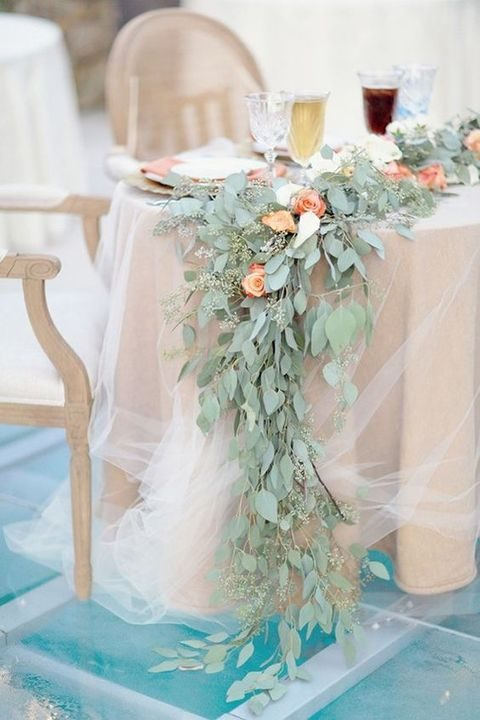a rose and eucalyptus garland on a tulle covered sweetheart table for a spring wedding