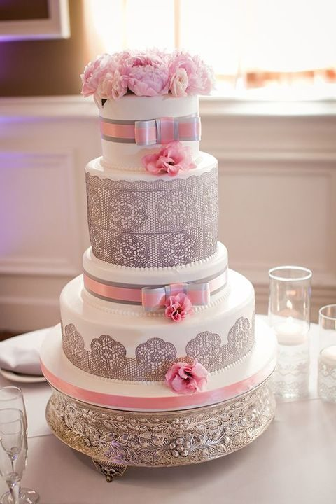 a white cake with grey lace decor and pink flowers