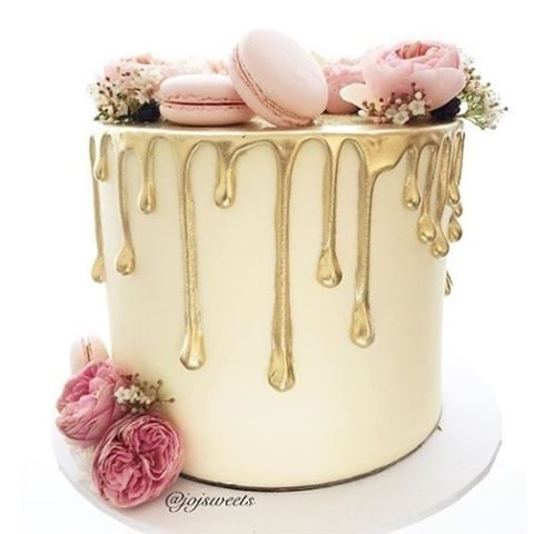 beautiful drip cake with pink macarons