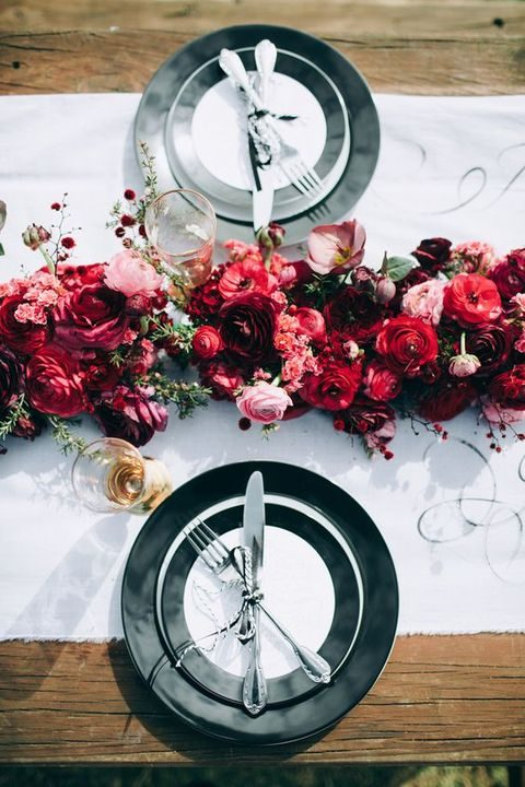 black and white table decor with a bold red floral table runner